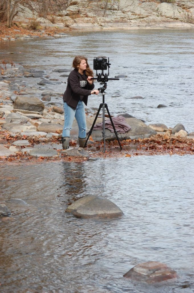 Woman standing in the creek taking pictures
