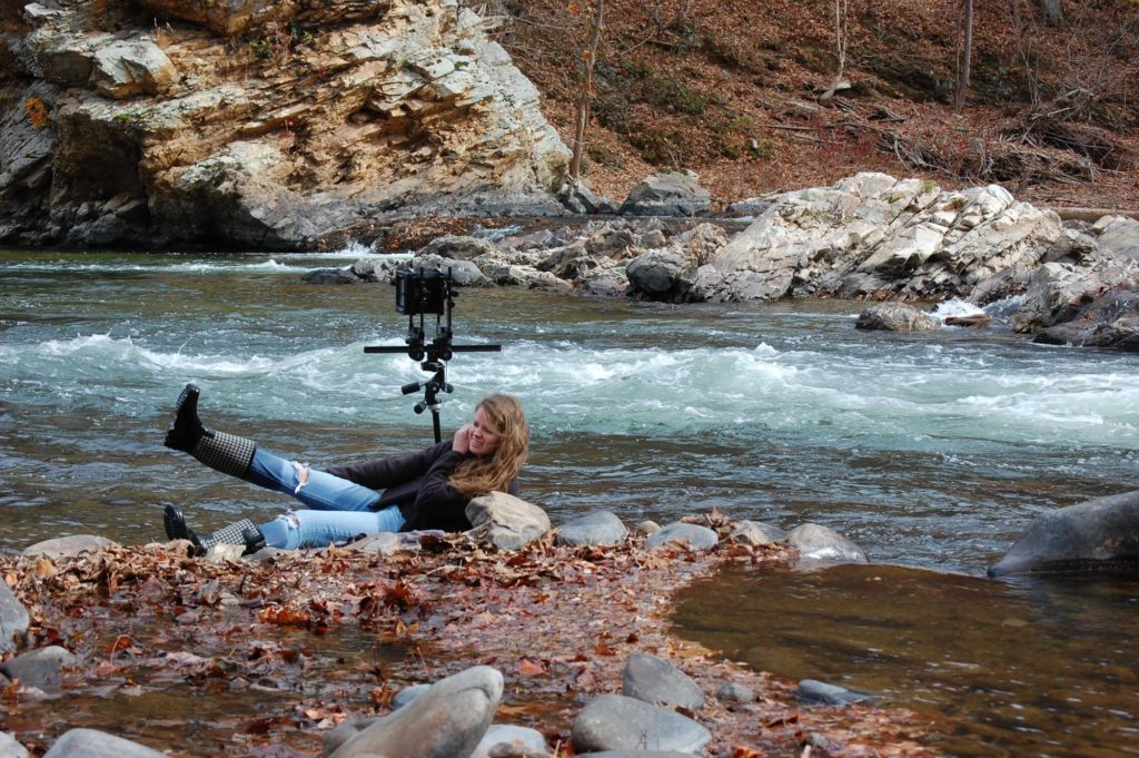 Woman falling down in the creek while taking pictures