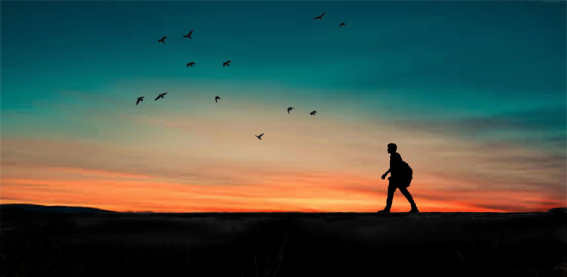 A person walking in front of the sunset