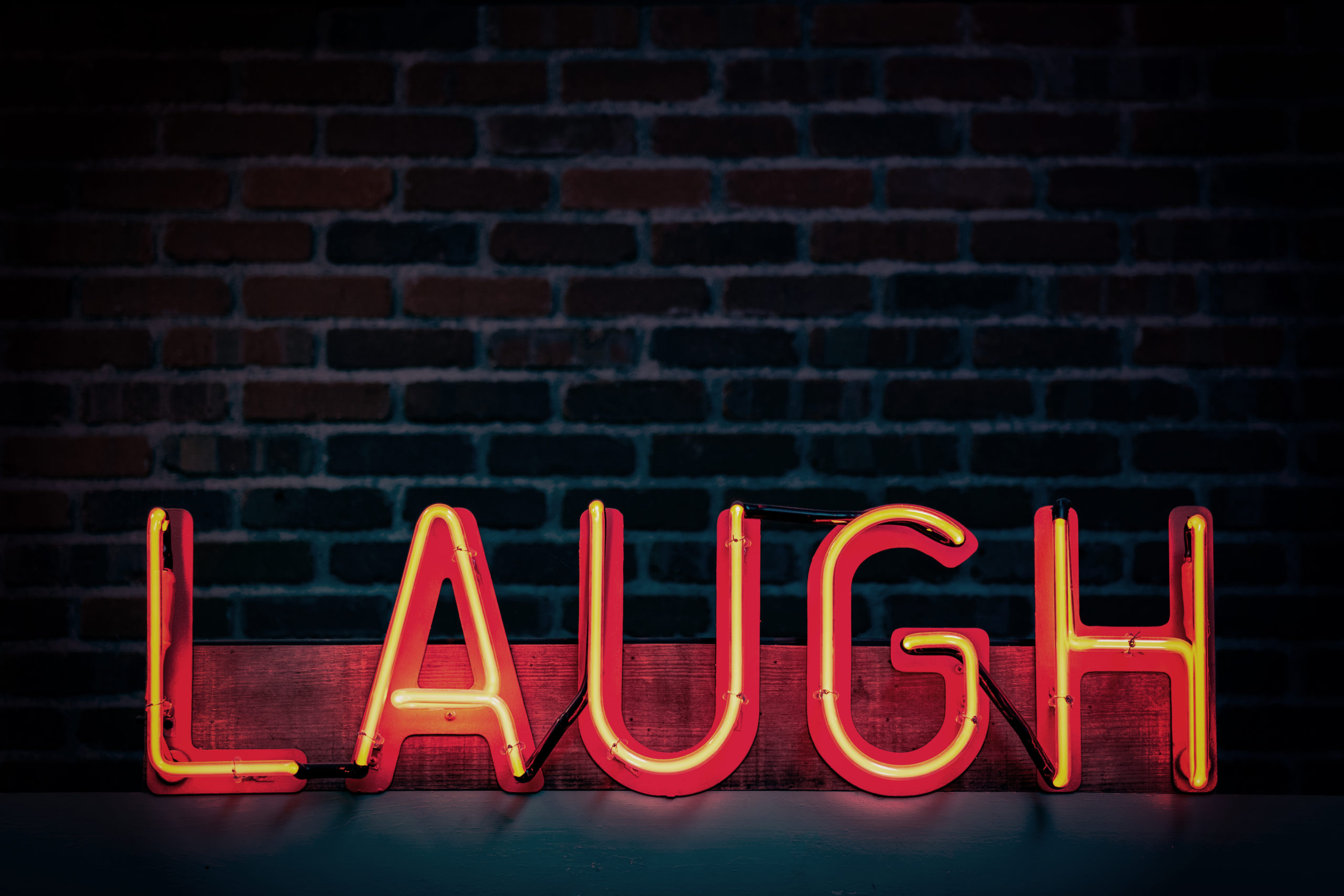 Neon sign that says laugh