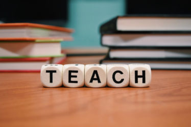 The word teach spelled with blocks