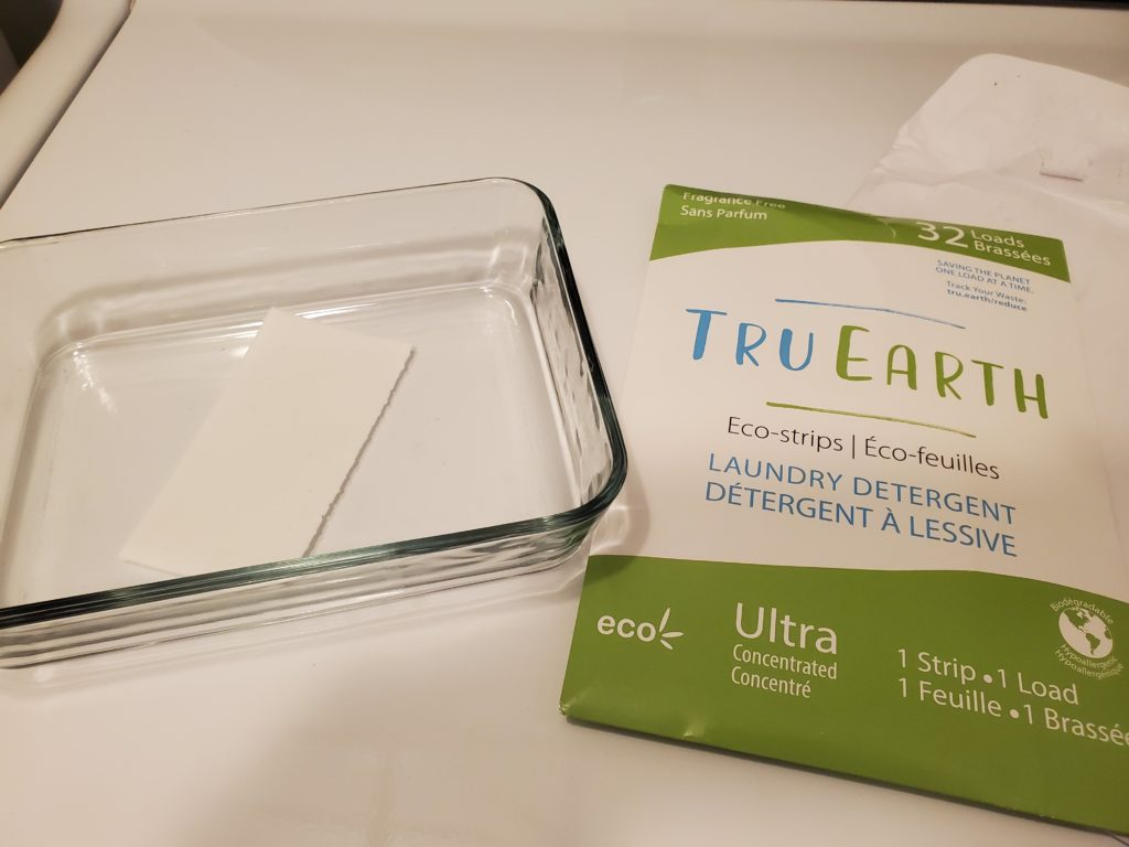 Tru Earth Laundry Strips package and container with one strip in it.