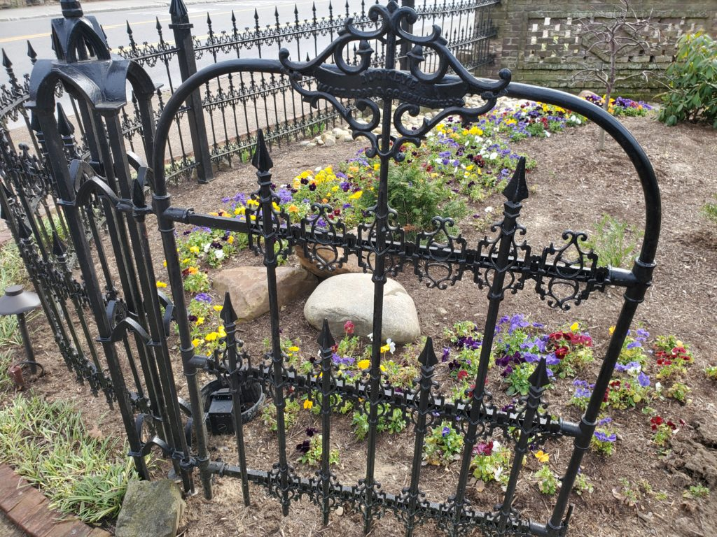 An open gate in front of a flower garden